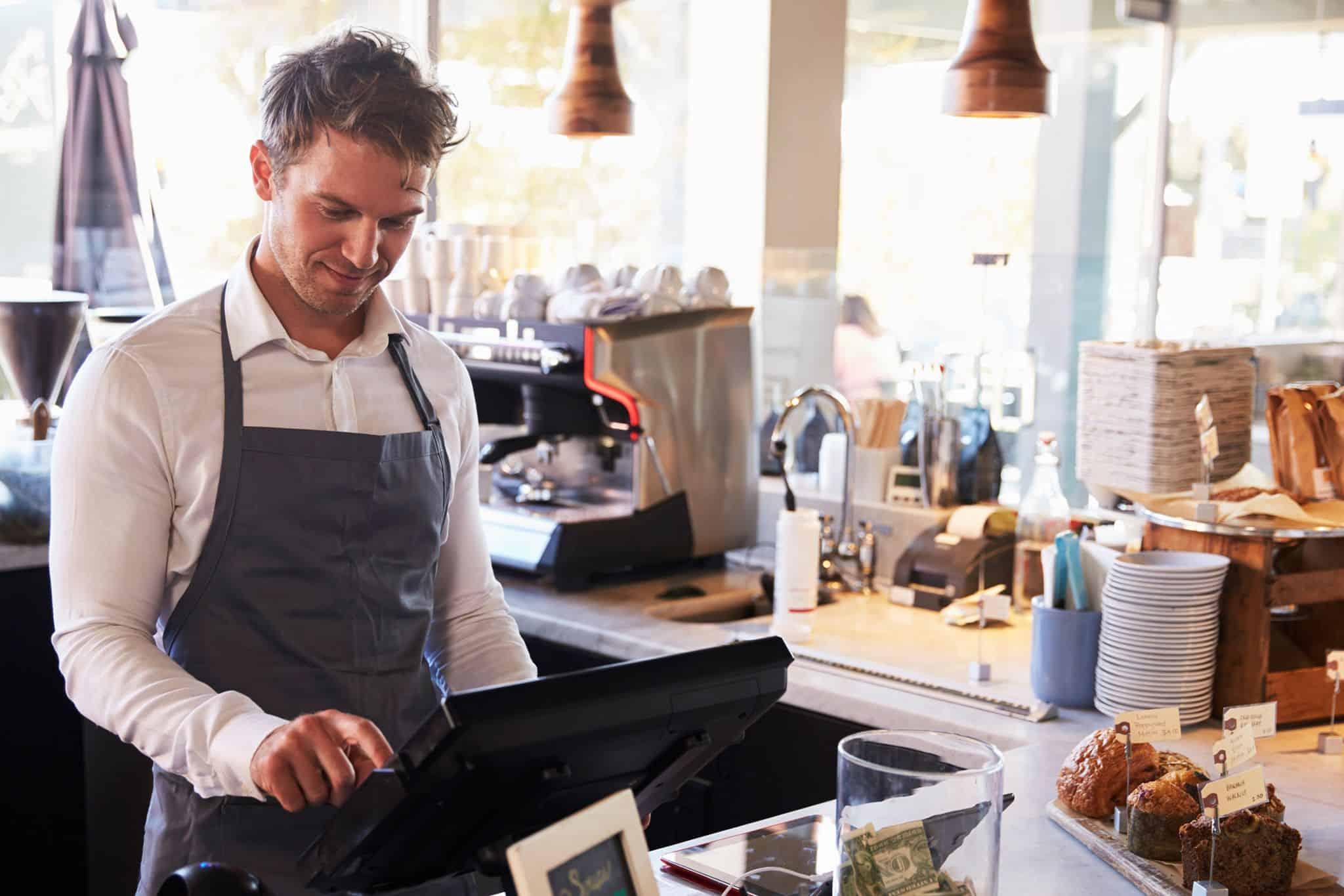 Bilde av mann som jobber i kafe med kassen - kassekontroll